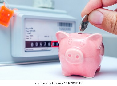 Person's hand with coin and pink piggy bank near a gas meter at home. Symbolic image of cost, energy efficiency and saving natural gas at home.