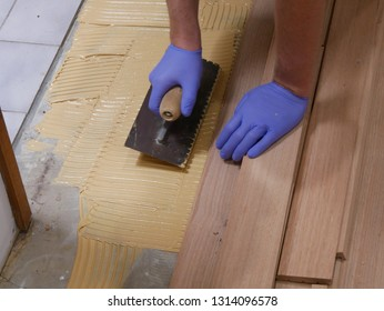A persons hand with gloves holding a notched trowel spreading a brown glue on a concrete floor with pieces of hardwood floor timber reading to lay the hardwood floor in a house renovation, Australia