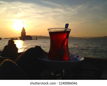 Person's hand holding a cup of red Turkish tea in front of the sea at sunset with kiz kulesi in the background, Istanbul travel photography - Shutterstock ID 1240086046