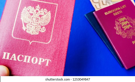 Persons hand holding passport on blue background. Citizenship of Estonia and Russia. Citizenship of European Union (EU) and Russian Federation. Top view. Copy space design. Rubles and Euro banknotes.