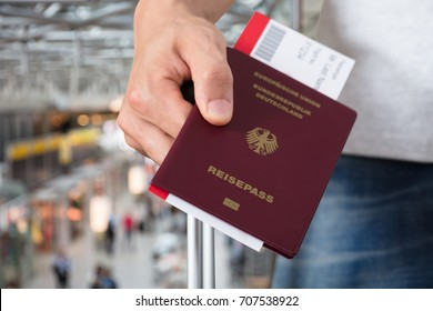 Person's Hand With Luggage Holding Passport And Boarding Pass Tickets At Airport