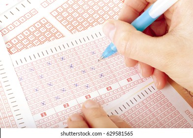 Person's Hand Marking Number On Lottery Ticket With Pen