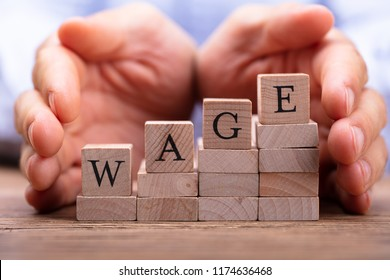 Person's Hand Protecting Wage Text On Wooden Blocks On Wooden Table