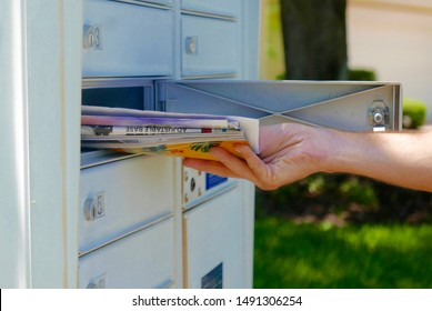 Person's hand pulling a pile of junk mail out of an outdoor community mailbox