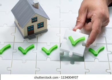 A person's hand solving check mark puzzle near house model