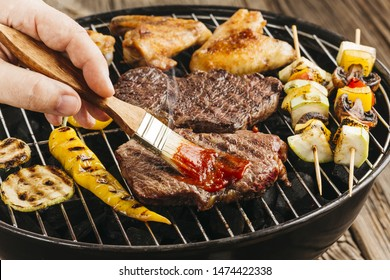 A person's hand spreading sauce on grilled steak over barbecue