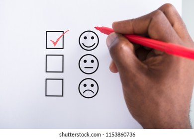 Person's Hand Ticking Off Checked Box Near The Smile Emoji With Red Pen