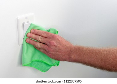 Persons hand wiping a wall white light control. Inside white wall light switch cleaned with a cloth. Indoor flat white light switch being cleaned by a hand with a rag as some house cleaning chores.