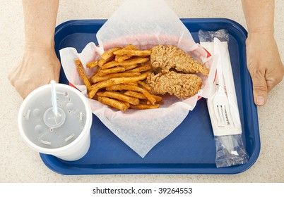 Person's hands holding a tray with an unhealthy, fried, fast food meal.