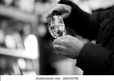 Person's hands pouring bubbly champagne into a glass, monochrome