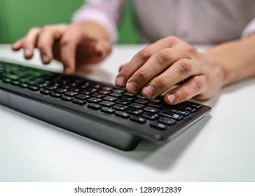 A person's hands typing on a black keyboard while working.