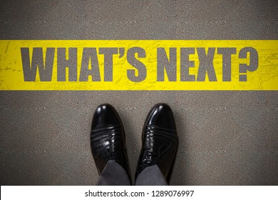 Person's Standing Next To What's Next Text On Asphalt Background