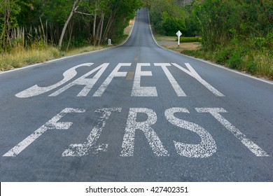 Perspective of asphalt road with safety first text, message on the road. Concept of safe driving and preventing traffic accident.