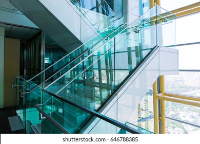 Perspective beside marble and glass staircase in business office.