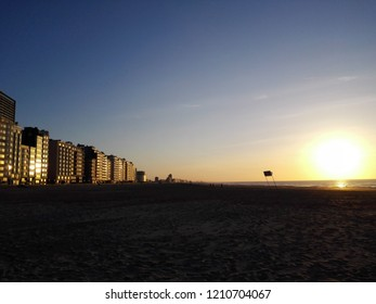Perspective of a deserted sandy beach of Ostend at sunset, Belgium