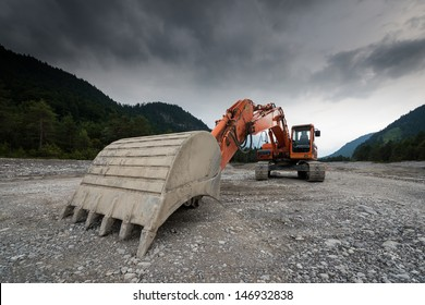 perspective of digger power shovel in red on gravel