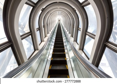 perspective escalators stairway inside contemporary blue glass business centre, concept of successful career elevation