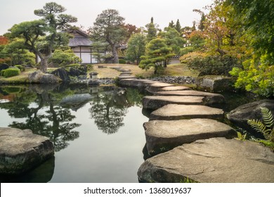 Perspective with large flat rocks forming a path over the pond and with a stone lantern and a Japanese building in background, in autumn, at Koko-en Garden in Himeji located next to the famous castle.