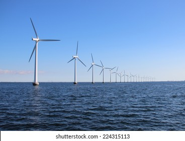 Perspective line of ocean wind mills with dark water and sky