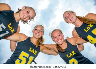 Perspective looking up with team of girls lacrosse players huddled close together, arms on each others shoulders, smiling and looking down at the viewer.