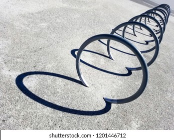 Perspective of metal hoops to park bicycles with its reflected shadows