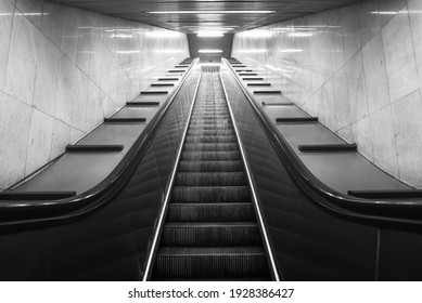 Perspective of mobile staircase in Milan's underground station. Light at the end of the tunnel. Monochromatic.