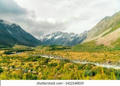 Perspective of Mount Cook from the Hooker trail tramping trek. Dramatic. Snow capped Mountain background. Grey cloudy moody. Green outdoors nature concept. Shot in Pukaki South Island, New Zealand, NZ