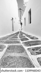 Perspective of a narrow street in Mykonos, Greece. Black and white image