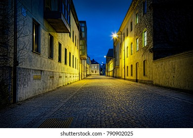 Perspective night view of a empty urban cobblestone street with moody lights in Lund, Sweden. Tranquil feeling of silence.