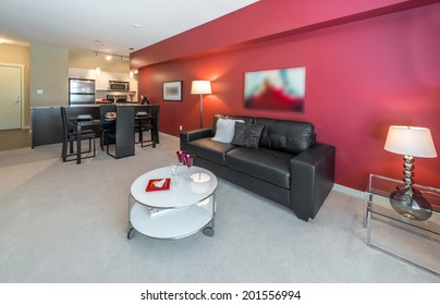 Perspective, outlook at the luxury living suite of brand new house: nicely decorated  living room with red walls, leather couch, coffee and dining tables and the kitchen at the back. Interior design.