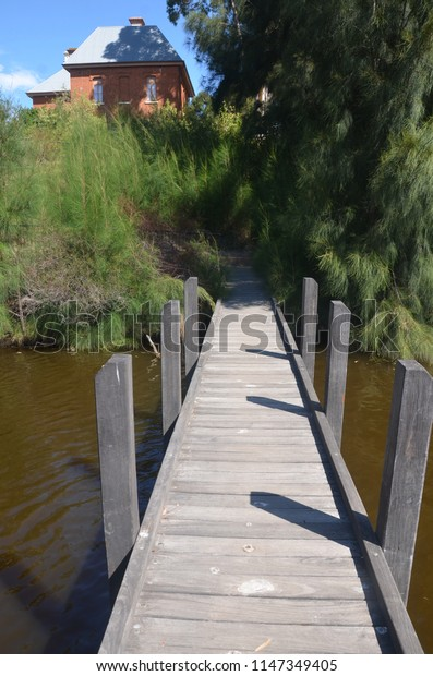 Perspective photography of a bridge overseeing a lake and grape farm.