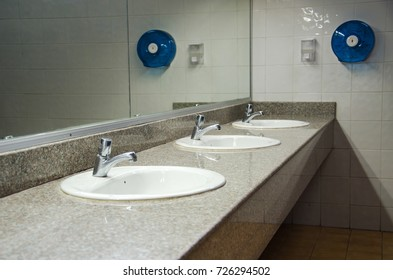 Perspective of public restroom show the mirror, sinks, sanitary, tissue paper box and hand soap bottle at the school.