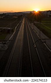 Perspective of the railroad tracks, backlit, with a sunset in the background