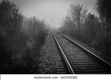Perspective of railway track disappearing in mist in foggy morning - monochrome image