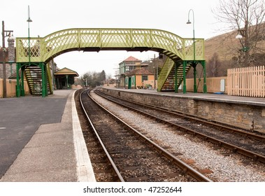 A perspective of railway tracks diverging in the distance with a footbridge framing the old station and platforms