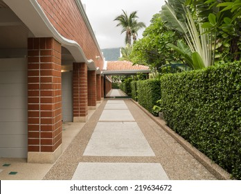 Perspective resort way between brick  wall and green garden.