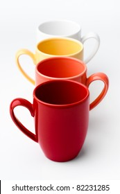 Perspective row of bright colorful mugs, red, orange, yellow and white, on a white background