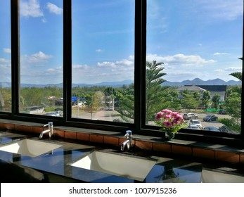 Perspective scene of public restroom that have basin and a vase of pink flower decoration and a good view of natural environment of sky, mountain and tree that can look outside from big window