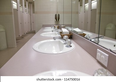Perspective shot of a counter-top with five sinks and mirrors