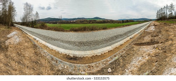 A perspective shot of an under construction railway track with stones laid out uniformly surrounded by a countryside view on one side, mud and stones on the other