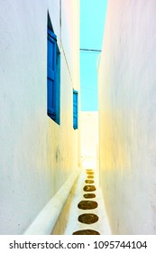 Perspective of small narrow alley in Mykonos, Greece
