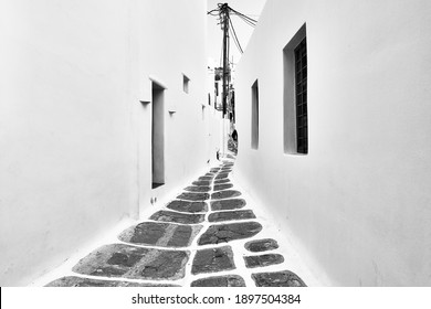 Perspective of a street between traditional whitewashed houses in Mykonos town (Chora), Greece. Greek architecture. Black and white photography
