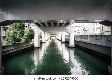 Perspective view with beautiful daytime filtered light at the River Canal under Hanshin Expressway Number 1, Namba, in downtown Osaka, Japan.