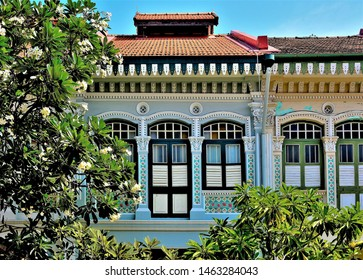 Perspective view of beautiful vintage traditional Singapore Peranakan or Straits Chinese shop house exteriors with antique wooden shutters framed by Frangipani in historic Joo Chiat, Singapore.