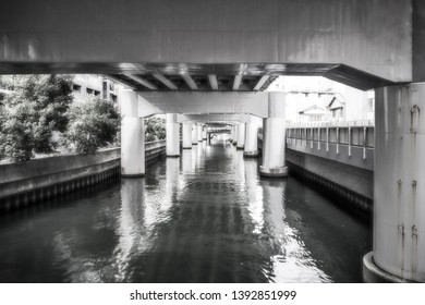 Perspective view in black and white with beautiful filtered light at the River Canal under Hanshin Expressway no1, Namba in downtown Osaka, Japan.