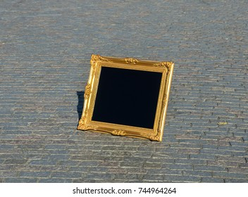 Perspective View of Blank Golden Square Frame in Vintage Design on Gray Brick Stone Street Road. Sidewalk, Driveway, Pavers, Pavement used as Template to mock up, display picture or Text in the Frame