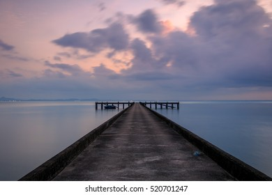 Perspective view of a cement pier on the sea at sunset with perfectly specular reflection