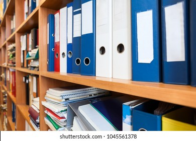 Perspective view at of colourful binders sorted on office shelves, archive