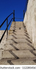 Perspective view of the concrete staircase & iron railings on the esterior of the Manitowoc lighthouse on Great Lake Michigan with a deep blue sky. Capture of light and shadows on a sunny afternoon.