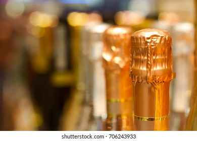 perspective view detail of golden champagne bottles tops arranged in store shelf
